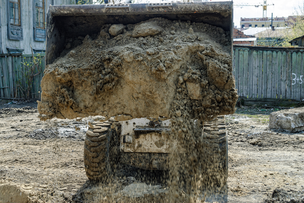 Skid loader on road construction